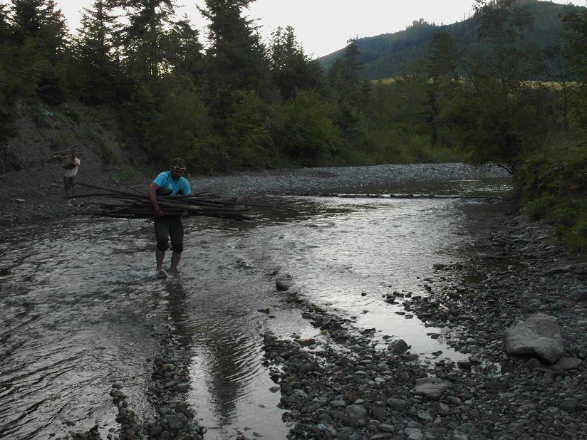 Towarzystwo niesie przez rzekę dary lasu